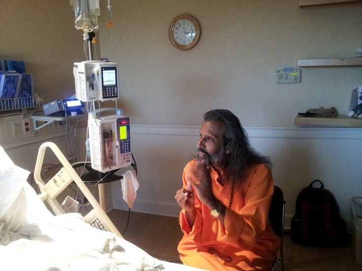 Swami visiting with a patient in the hospital who had requested time with him.